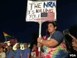 Protesters hold anti-NRA signs, June 12, 2016. (K. Gypson/VOA)