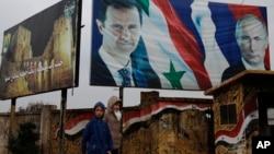 FILE - Syrians walk past posters of Syrian President Bashar al-Assad and Russian President Vladimir Putin, in Aleppo, Syria, Jan. 18, 2018.