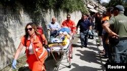 Petugas medis mengangkut korban luka-luka akibat gempa di Pescara del Tronto, Italia tengah, Rabu (24/8).