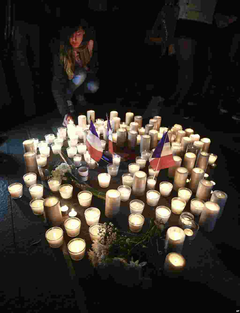 A young woman places candles a circle during a vigil in a tribute to the victims of the Bastille Day attack, in Sydney, Australia on July 15, 2016.