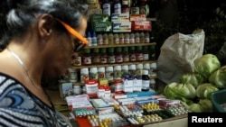 A woman walks past a fruit and vegetables stall selling medicines at a market in Rubio, Venezuela, Dec.r 5, 2017.