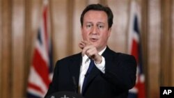 Britain's Prime Minister David Cameron gestures during a press conference in Downing Street in London, where he said aid worker Linda Norgrove, 36, who died in Afghanistan during a rescue attempt, may have been killed by her American rescuers, rather than