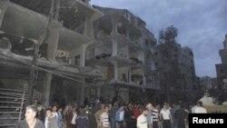 Warga mengamati bangunan yang hancur pasca ledakan bom mobil di Daf al-Shok, Damaskus, Suriah (26/10).