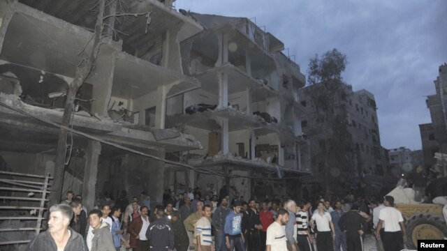 A crowd gathers in front of damaged buildings after a car bomb exploded at Daf al-Shok district, in Damascus, Syria, October 26, 2012, in this photograph released by Syria's national news agency SANA.