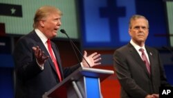 Republican presidential candidate Donald Trump speaks as Jeb Bush watches during the FOX News Channel Republican presidential debate at the Quicken Loans Arena Thursday, Aug. 6, 2015, in Cleveland.