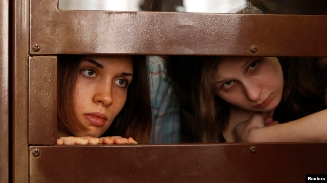 "FILE - Nadezhda Tolokonnikova (L) and Maria Alyokhina, members of female punk band ""Pussy Riot,"" look out from a defendants' cell in a Moscow courtroom July 30, 2012."