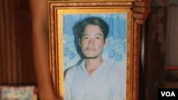 An unknown person holds a photo of Tuy Sros, 34, in a home in Banteay Meanchey province's Ou Chrov district's Chrey village, Phnom Penh, Cambodia, January 20, 2020. (Sun Narin/VOA Khmer)