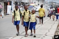 FILE - School children walk in the street in Lagos, Nigeria, June 17, 2014.