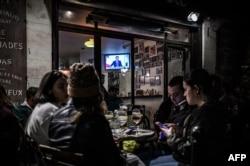 Para pengunjung kafe di Bordeaux, Perancis selatan, menikmati suasana di teras kafe tersebut, sambil menyimak pidato Presiden Emmanuel Macron soal restriksi baru untuk menekan laju penularan virus Covid-19, Rabu malam, 28 Oktober 2020.
