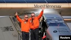 Andre Borschberg (à droite), le pilote suisse de Solar Impulse 2, est salué pour le pilote suisse Bertrand Piccard après avoir atterri au Caire, Egypte, le 13 juillet 2016.