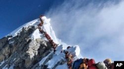 In this photograph from May 22, 2019, a long line of climbers move through the Everest 'death zone.' (Nimsdai Project Possible vía AP)