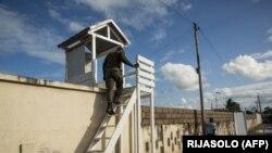 Des policiers surveillent l'entrée d'un abri pour les personnes infectées par le coronavirus à Toamasina, Madagascar, le 3 juin 2020. (Photo by RIJASOLO / AFP)