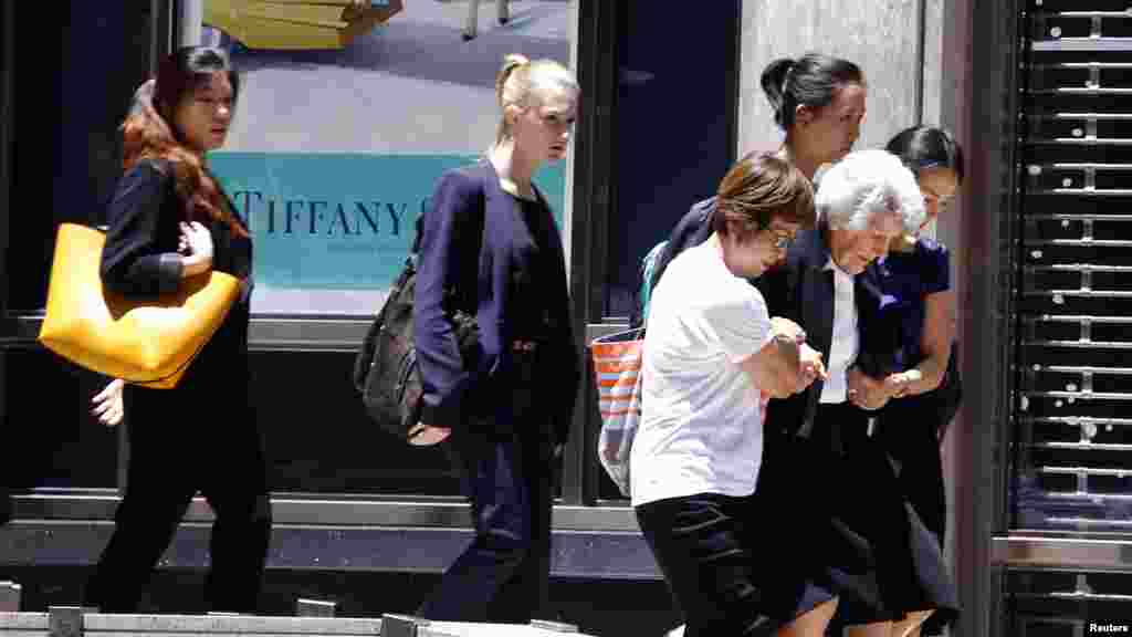 A woman is assisted as a group of people are evacuated by police from a building next to Lindt cafe in Martin Place, where hostages are being held, in central Sydney, Australia, Dec. 15, 2014.