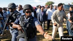 FILE - Members of a security team escort Lesotho politician Thomas Thabane (center, in background) after he cast his vote during the country's national elections in Magkhoakhoeng village, outside the capital Maseru, Feb. 28, 2015. Thabane's estranged wife, Lipolelo Thabane, was shot dead Thursday by unknown assailants.