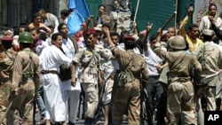 Soldiers hold back supporters of Yemen's President Ali Abdullah Saleh during clashes with anti-government protesters in the southern city of Taiz, Apr 22 2011