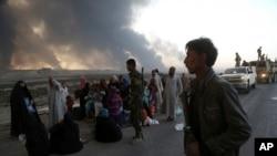 De la fumée s'élèvent alors que les habitants évacuent la ville à Mossoul, Irak, le 18 octobre 2016.