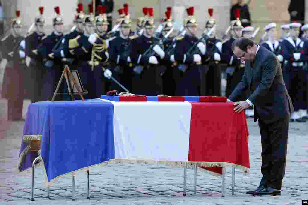 French President Francois Hollande pays his respect at the coffin of one of the two soldiers that died on Dec. 9 in Central African Republic, at the Invalides in Paris.