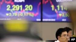 A currency trader watches the computer monitors near the screens showing the Korea Composite Stock Price Index (KOSPI), left, and the foreign exchange rate between U.S. dollar and South Korean won at the foreign exchange dealing room in Seoul, South Korea