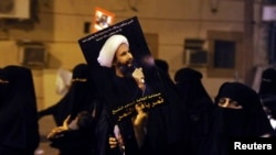 FILE - Protester holds up a picture of Sheikh Nimr al-Nimr during a rally in coastal town of Qatif, Saudi Arabia.