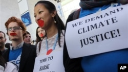 Local and international activists march inside a conferences center to demand urgent action to address climate change at the U.N. climate talks in Doha, Qatar, December 7, 2012.