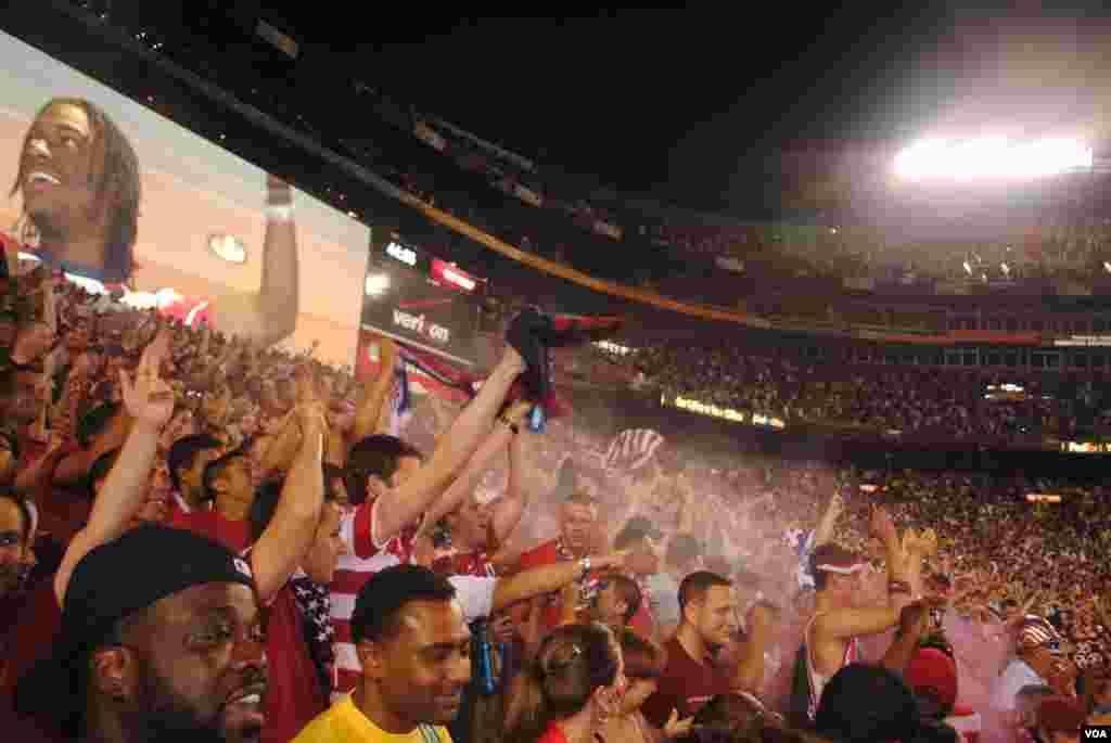 Seguidores del equipo de EE.UU. celebran el gol de Herculez Gomez en el minuto 45, alcanzando un puntaje de 2-1 liderando Brasil. VOA/M. Lipin