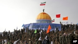 Members of the Basij, the paramilitary unit of Iran's Revolutionary Guard, gather around a replica of Jerusalem's gold-topped Dome of the Rock mosque as one of them waves an Iranian flag from on top of the dome during a military exercise, outside Qom, Iran, Nov. 20, 2015.