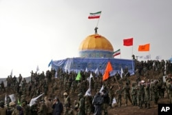 Members of the Basij, the paramilitary unit of Iran's Revolutionary Guard, gather around a replica of Jerusalem's gold-topped Dome of the Rock mosque as one of them waves an Iranian flag from on top of the dome during a military exercise, Nov. 20, 2015.