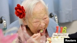 FILE - Japanese Misao Okawa, the world's oldest woman, eats her birthday cake as she celebrates her 116th birthday in Osaka, western Japan, in this photo taken by Kyodo March 5, 2014.