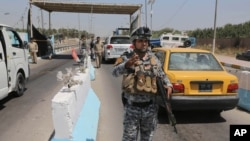 Iraqi federal policemen stand guard at a checkpoint in Baghdad, Iraq, June 22, 2014.