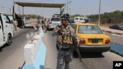 6月22日伊拉克警察在首都巴格达的一个检查站执行任务