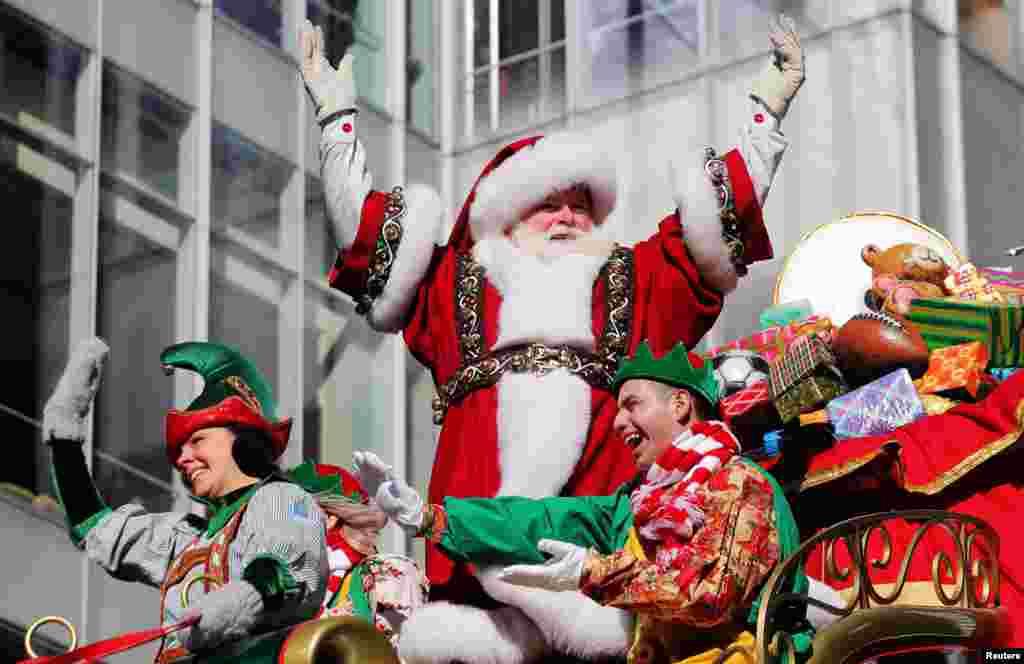 Santa Claus បកដៃស្វាគមន៍អ្នកចូលរួមទស្សនាព្រឹត្តិការណ៍ហែក្បួននៅថ្ងៃបុណ្យ Thanksgiving លើកទី៩២របស់ហាង Macy នៅទីក្រុង New York ថ្ងៃទី២២ ខែវិច្ឆិកា ឆ្នាំ២០១៨។