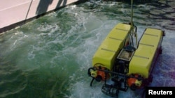 "FILE - A Deep Drone underwater surveyor is lowered from the United States Navy's USS Grapple during a ""wet check""."