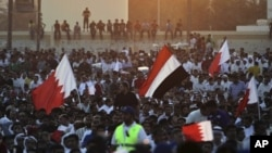 Supporters of the Shiite opposition Al-Wefaq society wave red-and-white Bahraini flags and a Yemeni flag during a rally in Tubli, Bahrain, near the capital of Manama, September 22, 2011.