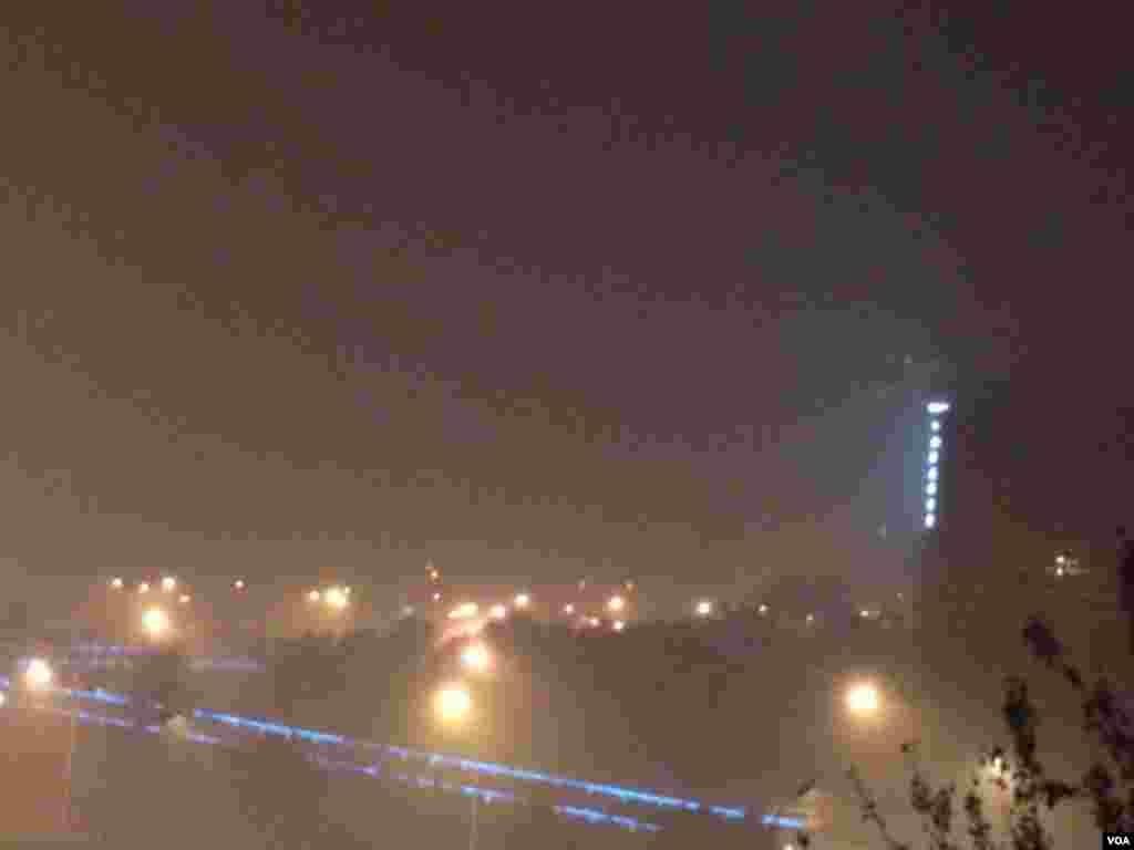2015年11月30日,夜幕下的北京东长安街上空,雾霾弥漫。人们被告诫注意防范呼吸道疾病,减少出行。(美国之音叶兵拍摄)