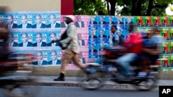 A wall is blanketed with campaign posters promoting electoral candidates, in Port-au-Prince, Haiti, Oct. 7, 2015.
