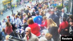 A still image captured from surveillance video at the Boston Marathon shows the scene moments before a second bomb exploded as a man, marked with a circle by prosecutors (top R) and identified by them as defendant Dzhokhar Tsarnaev, moves rapidly away from the spot near the finish line of the race, April 15, 2013, in this handout video provided by the U.S. Attorney's Office in Boston, March 9, 2015.