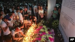 Mourners in the Philippine capital, Manila, light candles and lay flowers in front of a memorial outside the Resorts World Manila entertainment complex, June 3, 2017. On Friday, a gunman entered the complex and set fire to its casino, triggering a blaze that left at least 38 people dead.