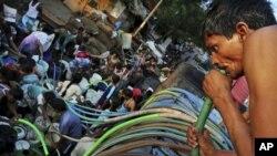 Seorang warga New Delhi mengisap air dari selang sementara yang lainnya mengantri air akibat kekeringan di kota itu. (Foto: AP)