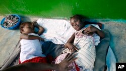 A father comforts his daughter as she receives treatment for cholera alongside another little girl, on the floor of a small and overwhelmed health clinic in Anse d'Hainault, southwestern Haiti, Friday, Oct. 14, 2016.