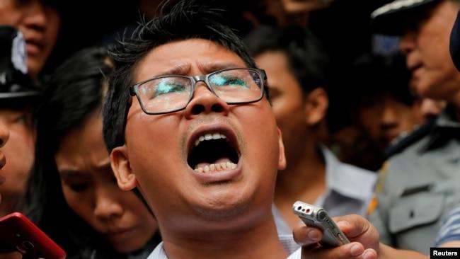លោក Wa Lone (កណ្តាល) ដែលជាអ្នកកាសែតរបស់បណ្តាញសារព័ត៌មាន Reuters និយាយទៅកាន់អ្នកកាសែតនានា ខណៈដែលលោកត្រូវបានប៉ូលិសនាំខ្លួនចេញពីតុលាការក្នុងទីក្រុង Yangon ប្រទេស មីយ៉ាន់ម៉ា កាលពីថ្ងៃទី ៣ ខែ កញ្ញា ឆ្នាំ ២០១៨។ តុលាការក្នុងប្រទេស មីយ៉ាន់ម៉ា បានកាត់ទោសអ្នកកាសែត Reuters ពីរនាក់ ឲ្យជាប់ពន្ធនាគាររយៈពេល៧ឆ្នាំ ចំពោះការរក្សាទុកឯកសារផ្លូវការដោយខុសច្បាប់ ដែលសាលក្រមនេះត្រូវបានធ្វើឡើង ខណៈដែលសហគមន៍អន្តរជាតិរិះគន់ទៅលើការចោទប្រកាន់ថា រដ្ឋាភិបាលមីយ៉ាន់ម៉ាបំពានសិទ្ធិជនជាតិរ៉ូហ៊ីងយ៉ា ដែលកាន់សាសនាឥស្លាម។ (AP Photo/Thein Zaw)