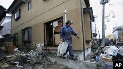 日本福岛县一位居民海啸过后在清理自家的院落