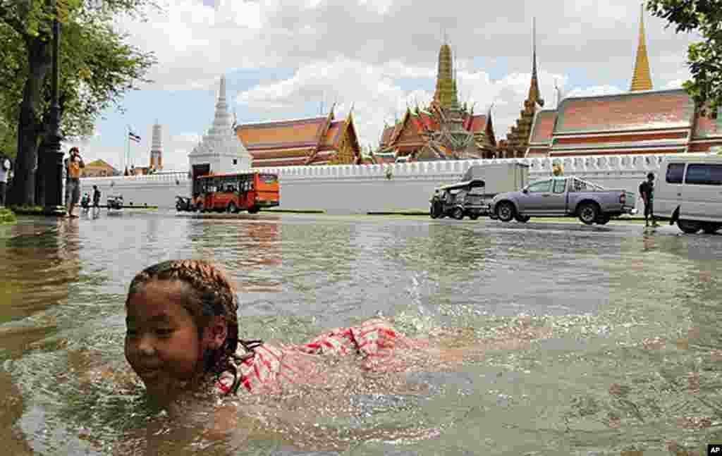 一名小女孩在曼谷大王宫前的大水中游泳嘻戏