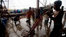 FILE - Migrant workers unload frozen fish from a boat at a fish market in Samut Sakhon Province, west of Bangkok, Thailand, June 20, 2014.