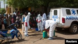 Health workers put on protective gear outside a mosque before disinfecting it, in Bamako, Mali, Nov. 14, 2014.