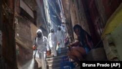Volunteers spray disinfectant in an alley to help contain the spread of the new coronavirus at the Santa Marta slum in Rio de Janeiro, Brazil, Saturday, Nov. 28, 2020.