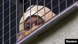 FILE - A migrant looks out the window in the facility for detention of foreigners in Bela-Jezova, Czech Republic, Nov. 5, 2015.