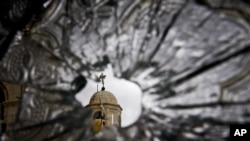A church dome seen through a broken window of the Sednaya Convent, which was damaged by artillery fire in Sednaya, north of Damascus, Syria. Christians, who make up about 10 percent of Syria's population of more than 22 million, say they are particularly vulnerable to the violence that has been sweeping the country since March 2011.