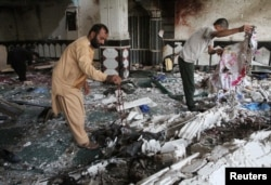 FILE - Relatives inspect the damage after an overnight suicide attack at a mosque in Herat, Afghanistan, Aug. 2, 2017.