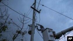En esta imagen, tomada el 12 de julio de 2018, un operario de la Autoridad de Energía Eléctrica de Puerto Rico trabaja para restaurar el suministro de energía eléctrica en Adjuntas, Puerto Rico. La red eléctrica de Puerto Rico arrastra problemas desde que Irma recorrió parte de la isla como un huracán de categoría cinco el 6 de septiembre, y luego del impacto directo de María, de categoría cuatro, dos semanas después, dañando hasta el 75% de las líneas de transmisión.