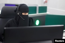 FILE - A Saudi woman works inside the first all-female call center in the kingdom's security sector, in the holy city of Mecca, Saudi Arabia, Aug. 29, 2017